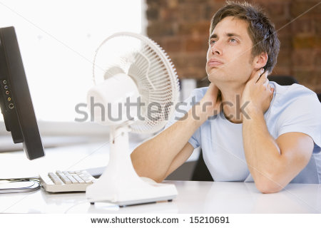 stock-photo-businessman-in-office-with-computer-and-fan-cooling-off-15210691