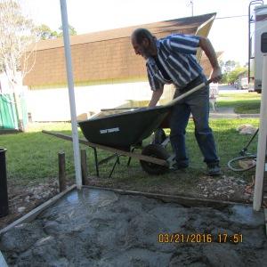 David mixing concrete in the wheelbarrow