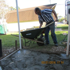 David mixing concrete in the wheelbarrow
