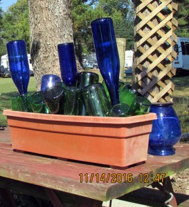 Green and blue bottles in planter