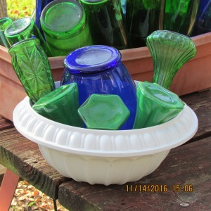 Blue vase with white planter and green vases